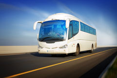 Bus in motion on the highway. White touristic bus in motion on the highway and blurred background Stock Image