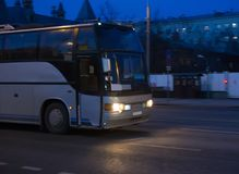 Bus moves on dark city street at night Stock Photos