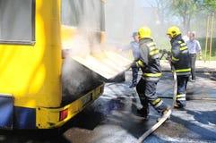 Bus op brand op de straat in het midden van de dag Stock Foto's