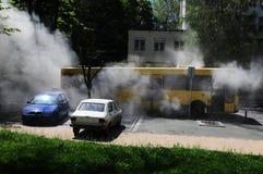 Bus op brand op de straat in het midden van de dag Stock Foto