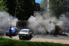 Bus op brand op de straat in het midden van de dag Stock Fotografie