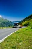 Bus op een weg in Alpen Stock Foto's