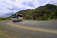 Bus op kronkelige weg in bergen Royalty-vrije Stock Foto