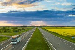 Bus op weg in mooi avondlandschap stock fotografie