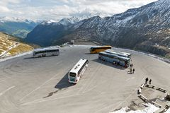 Bus parking lot on Grossglockner High Alpine Road in Austria. Coach buses parking lot with unrecognized tourists and the observation platform. High Alpine Road Royalty Free Stock Images
