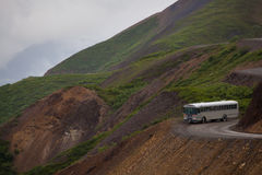 Bus près de falaise en stationnement national de Denali Photographie stock