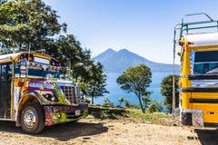 Bus pubblici & vista del lago Atitlan & dei vulcani, Guatemala fotografie stock libere da diritti