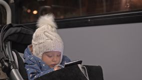Bus ride is not so boring with cartoons. Little two year old girl with smart phone sitting in stroller in the bus. Child watching cartoons on mobile during the stock video