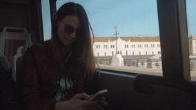 Bus ride with using cellphone. Young woman surfing the net on smart phone when traveling bus in the city stock footage