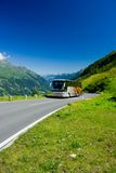 Bus on a road in Alps Stock Photos