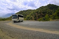 Bus on serpentine road in mountains. Tourist bus goes up the serpentine road in mountains in cloudy weather Royalty Free Stock Photo
