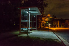 Bus shelter at night. Empty bus shelter at night.  Cars are parked down the road.  Letters are scratched into the glass Royalty Free Stock Photo