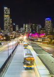 Bus station and modern buildings with light trail at night. Brisbane, Australia - September 26, 2016: Multiple exposure image of skyscrapers and light trail of Stock Photo