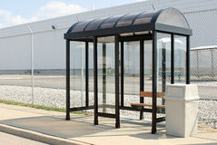 Bus Stop. Roadside bus stop with seat and trash receptacle Royalty Free Stock Photos