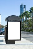 Bus Stop Billboard. Blank Bus Stop Billboard with Blue Building in Background royalty free stock photography