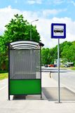 Bus stop with traffic sign. Bus stop with blank green billboard and blue traffic sign on street in cloudy summer day stock photo