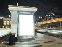 Bus stop at city night with blank white illuminated poster. Bus stop at city night with blank white illuminated poster next to road stock photo