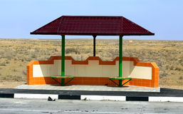 Bus stop in desert. Stopping place of public transport with a metal tent on a road in oriental desert area Stock Photography
