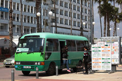 Bus stop in Larnaca, Cyprus. Larnaca, Cyprus - March 18, 2016: People at the intercity bus arrived to Finikoudes bus stop. Larnaca is the third largest city of Royalty Free Stock Photography
