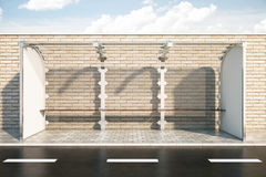 Bus stop. Modern glass bus stop in front of brick fence. Sky background. 3D Rendering Royalty Free Stock Images