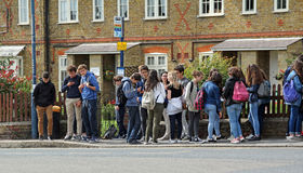 Bus stop queue. Photo of a group of school children waiting at a bus stop in whitstable high street kent england. photo taken 1st july 2016 ideal for diversity stock photos