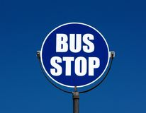 Bus stop sign. Round blue and white bus stop sign on a metal pole against a deep blue and perfectly cloudless summer sky Royalty Free Stock Photo