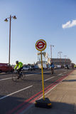 Bus Stop sign on the Blackfriars Bridge, cyclists in the background Stock Photos