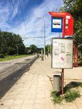 Bus stop sign and schedule. Neglected bus stop in a city Stock Image