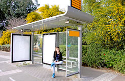 Bus stop. Teen age girl waiting alone for the bus Royalty Free Stock Images