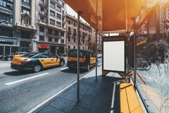 Signboard mockup on bus stop, taxicabs on the left. Bus stop in urban settings with white mock-up banner for advertising text; an empty billboard placeholder stock photo