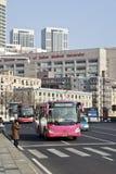 Bus sulla strada con l'ospedale sui precedenti, Dalian, Cina Immagine Stock Libera da Diritti