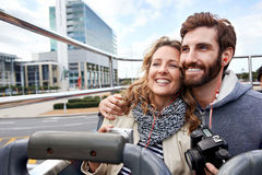 Bus tour of city. Tourist couple on open top bus tour guide around the city in vacation Royalty Free Stock Photos