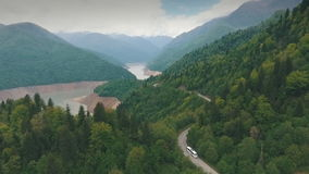 A bus traveling on a mountain road, mountain, aerial photography,shooting from a copter stock footage