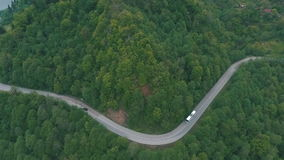 A bus traveling on a mountain road, shot from the air stock video