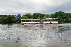 Bus trying to drive against flood on the street in Gdansk, Poland. Royalty Free Stock Images