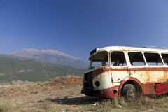 Bus wreck in arid landscape. Stripped rusty, old abandoned red bus wreck in arid mountainous landscape of Montenegro Royalty Free Stock Photos