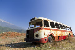 Bus wreck in arid landscape. Stripped rusty, old abandoned red bus wreck in arid mountainous landscape of Montenegro Royalty Free Stock Image