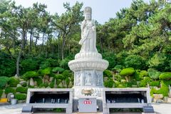 Guanyin or Guan Yin Goddess of Mercy white stone statue on the top of the hill at Haedong Yonggungsa Temple royalty free stock photo
