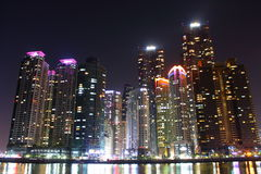 Busan, South Korea - March 26th of 2015: Night view of several buildings over the city's marine harbor. Royalty Free Stock Images