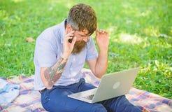 Buscar la inspiración El hombre barbudo con el ordenador portátil sienta el fondo de la naturaleza del prado Blogger inspirador p fotos de archivo libres de regalías