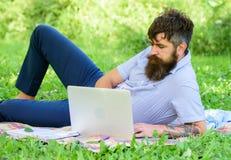 Buscar la inspiración Hombre barbudo con el fondo de relajación de la naturaleza del prado del ordenador portátil Programa de esc foto de archivo libre de regalías