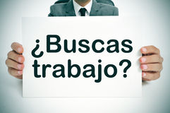 Buscas trabajo? are you looking for a job? written in spanish. A man wearing a suit holding a signboard with the question buscas trabajo? are you looking for a stock photo