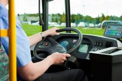 Buschauffeurzitting in zijn bus Stock Foto