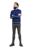 Buse uppsökt bärande träningsoverallomslag och jeans för grabb med korsade armar som bort ser royaltyfria foton
