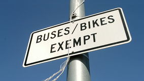 Buses, bikes exempt road sign on blue sky, stock footage