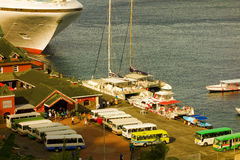 Buses and boats loading daytrippers from a cruise ship Stock Images