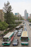 Buses and cars are moving on the road in Kunming, China Royalty Free Stock Image