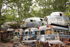 Buses and military aircraft in junkyard. Cockpit units of wrecked military aircraft on top of transport busses in junkyard Stock Image