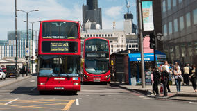 Buses near London Bridge. Two London buses reach the junction at the southern end of London Bridge Royalty Free Stock Image