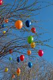 Bush with easter eggs and blue sky. Bush with colorful plastic easter eggs and blue sky, view from bottom up stock image
